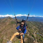 Paragliding in Pokhara with high angle aerial view of Pokhara valley, Sarangkot Hill and Annapurna range with blue sky in North Nepal's Paragliding 4 days package