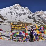 Trekkers posing picture along with Tibetan flag and name board, Mt. Annapurna I 8091m on background at Annapurna Base Camp.