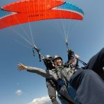 Paragliding in Pokhara over the sky above Sarangkot village with red parachute in North Nepal's Paragliding 4 days package