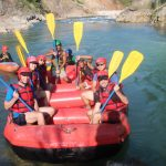 on the bank of river tourist are ready for rafting with an almost 8 member including guide.They are in pose to click the photo.Next to rafting boat there is kyaking boat.The water in river looks fresh, Upper seti river rafting.