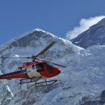 Red Helicopter flying in Everest region on March during Everest Base Camp Helicopter tour managed by North Nepal Travel