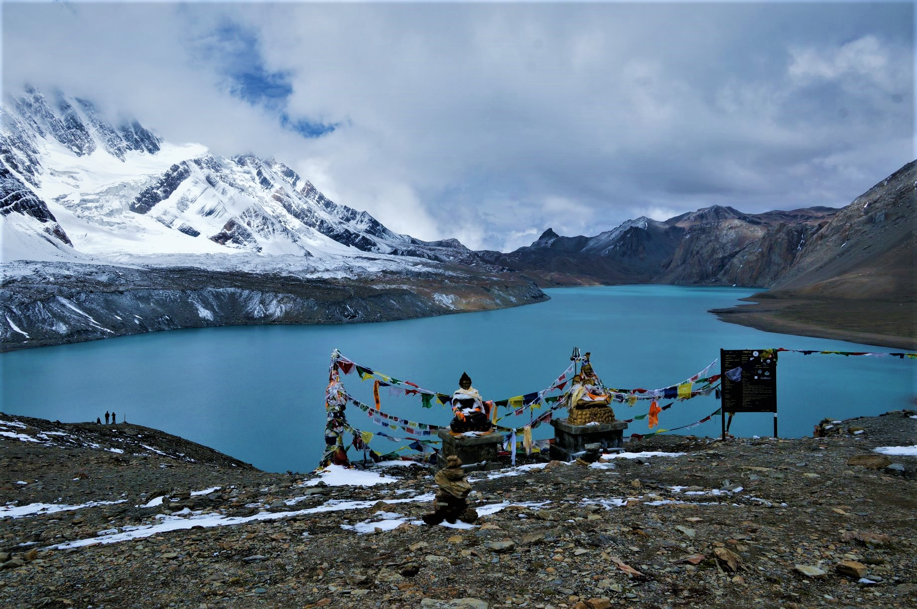 Hindu God Shiva & Buddha statues at the Tilicho Lake, covered with prayer's flags. Blue and calm surface of the lake, mountains covered in the shadow, sunlight in the back. Annapurna Circuit Trek, Nepal.