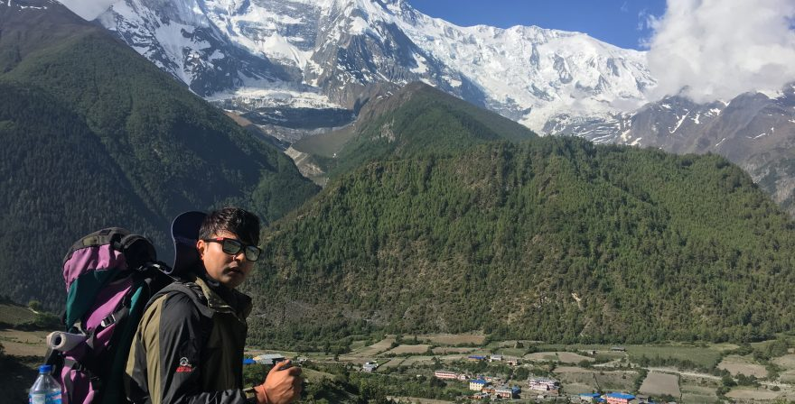 North Nepal Trekking guide on way to Ghyaru village from Upper Pisang, Mt. Annapurna IV and Lower Pisang village on background.